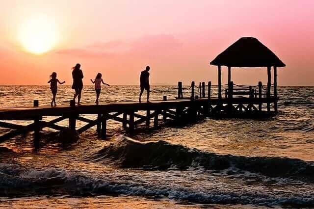 En familie springer på en kai i solnedgang
